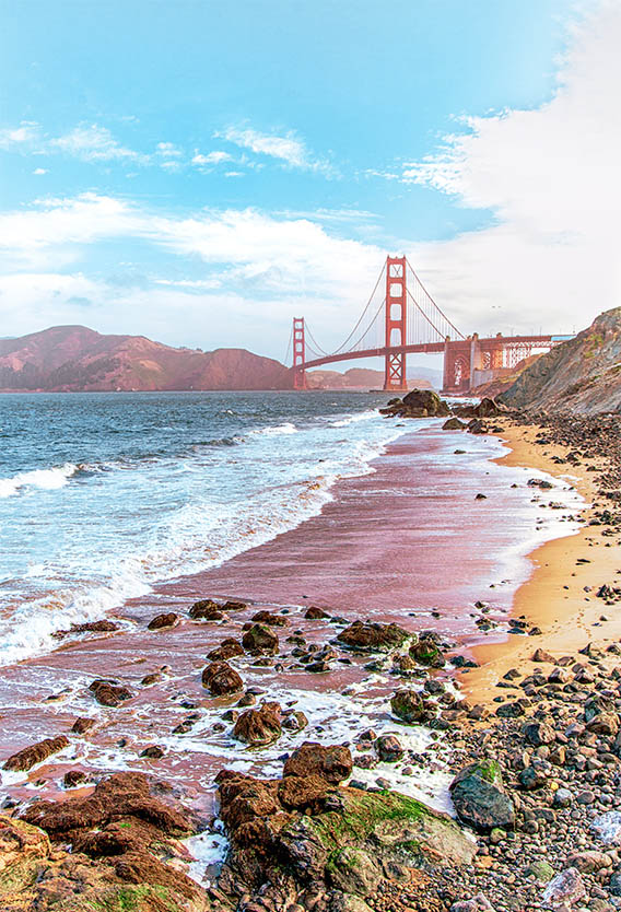 Rocky beach under cloudy blue skies with Golden Gate Bridge in the distance.