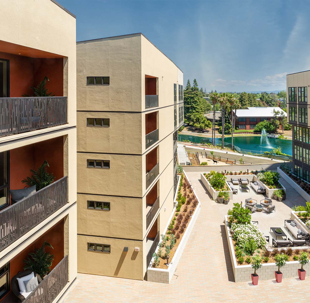 1250 Lakeside apartments overlooking outdoor lounge with lush landscaping and furniture.