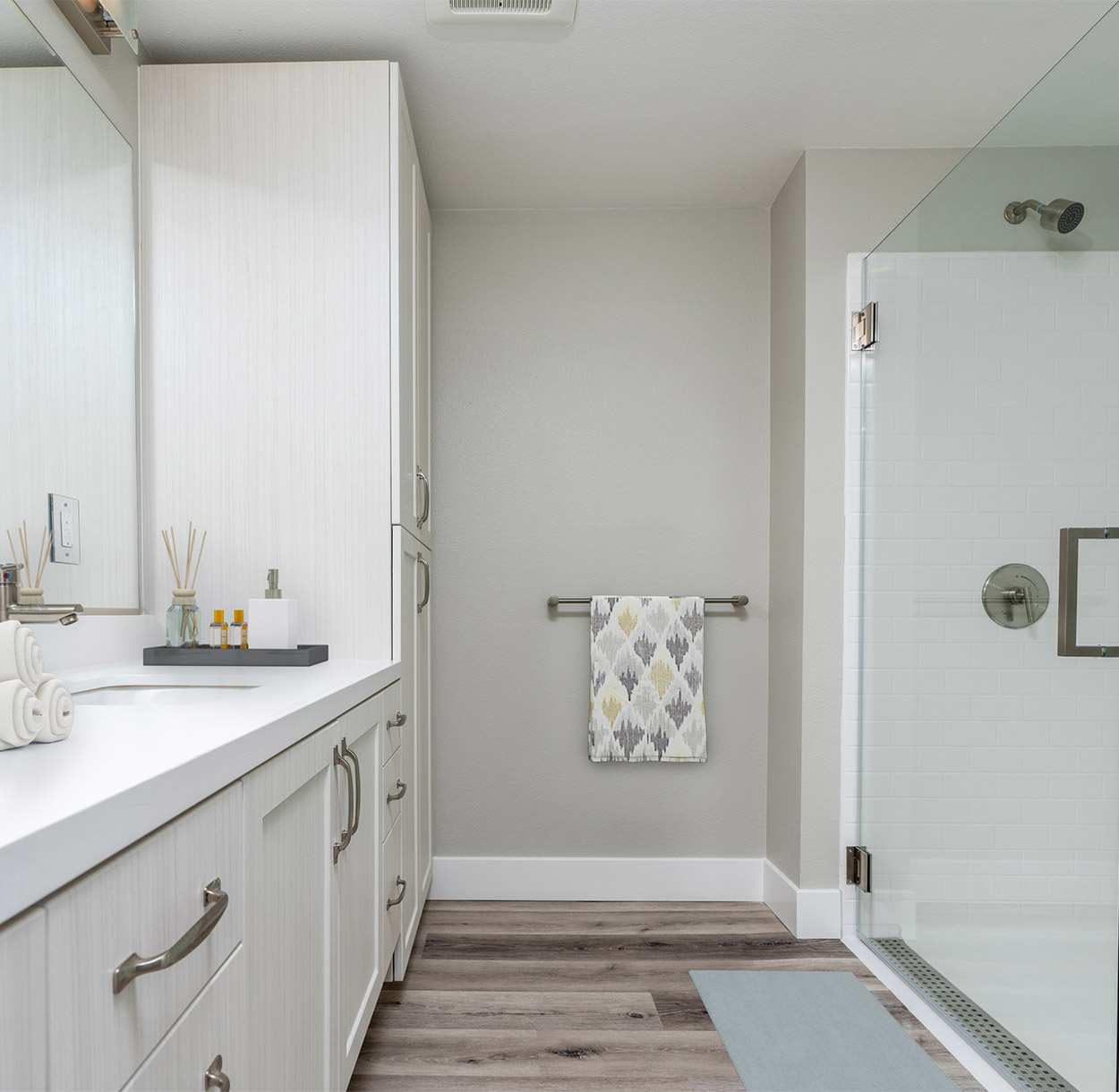 1250 Lakeside apartment bathroom with wood floor, white cabinets and counters, and glass walled shower.