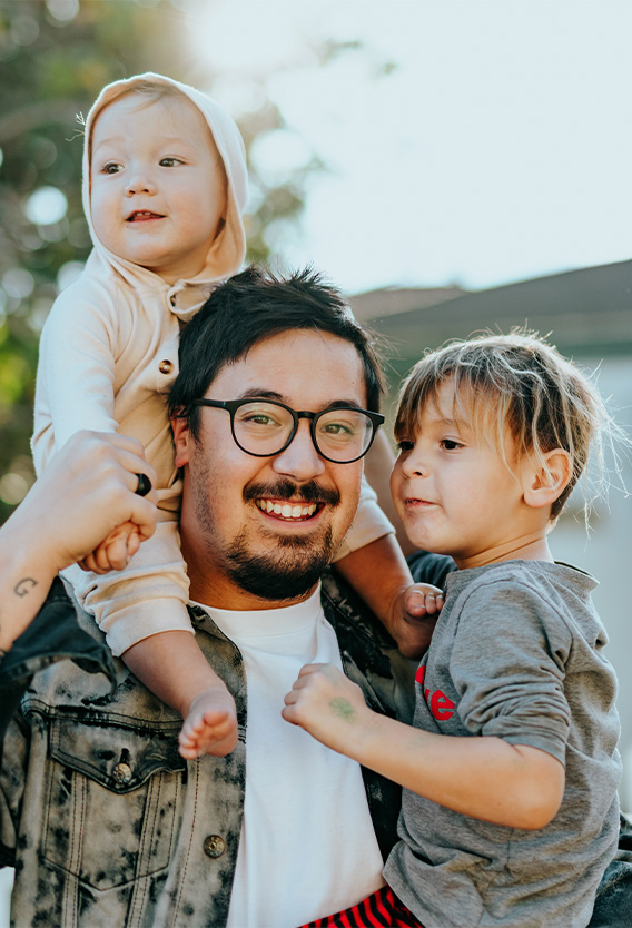 Person with glasses and bleached denim jacket with two children.
